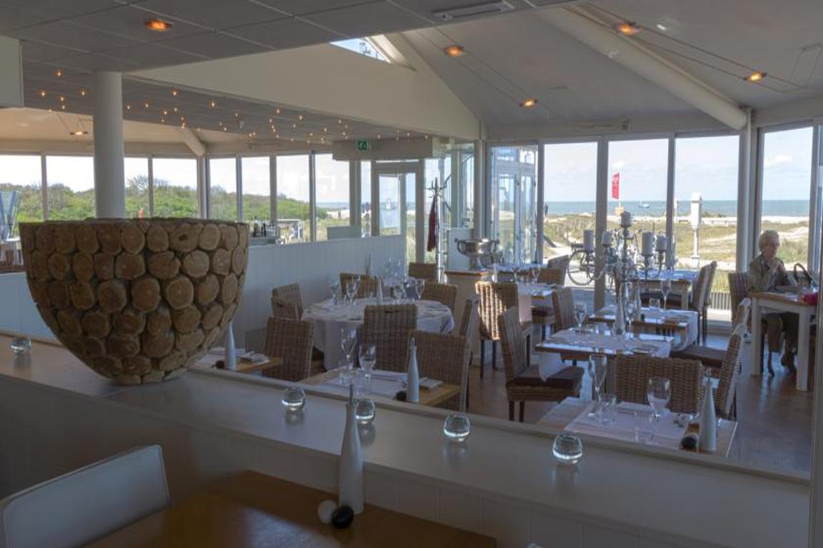 """Restaurant und Terrasse mit Blick auf Dünen und Meer im """"Beach Hotel & Spa Noordzee"""" in Cadzand-Bad"""